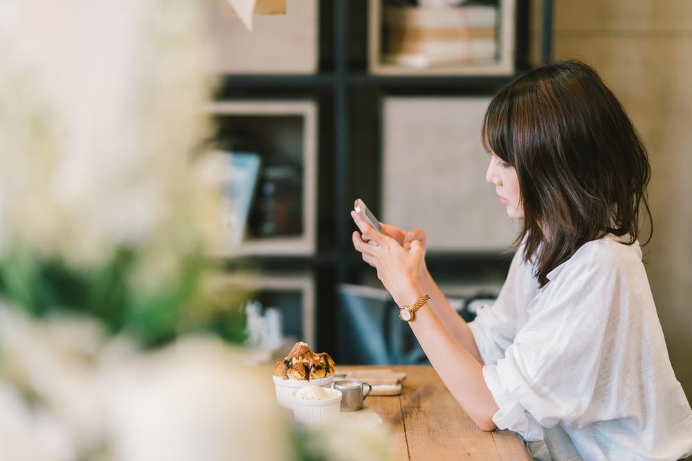 カフェで携帯を見ている女性